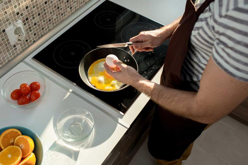 Płyta indukcyjna Amica czy też płyta elektryczna Amica, na której mężczyzna robi jajecznicę oraz opinie na jej temat, a także wady i zalety