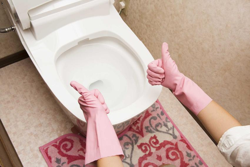 Dłonie w rękawiczka i odetkana toaleta, a także porady, jak odetkać kibel, czyli zatkaną toaletę krok po korku