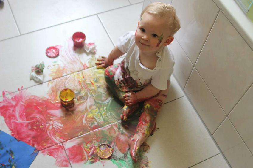 Dziecko ubrudzone farbą oraz porady, jak usunąć farbę z ubrania i jak sprać farbę z ubrania, czyli wywabianie plamy z farby czy usuwanie farby olejnej