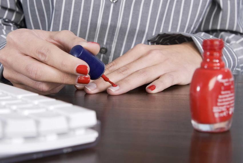 Kobieta malująca paznokcie oraz lakier do paznokci na ubraniu i porady, jak zmyć lakier do paznokci z ubrania i jak usunąć lakier do paznokci z ubrania