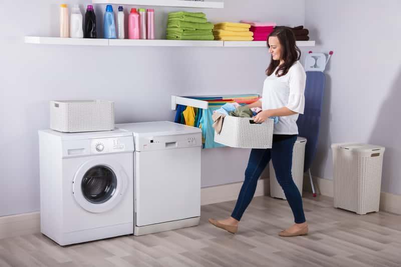 Kobieta wstawiająca pranie do suszarki elektrycznej do ubrań, a także suszarki elektryczne, wady, zalety, zastosowanie, rodzaje, jakość