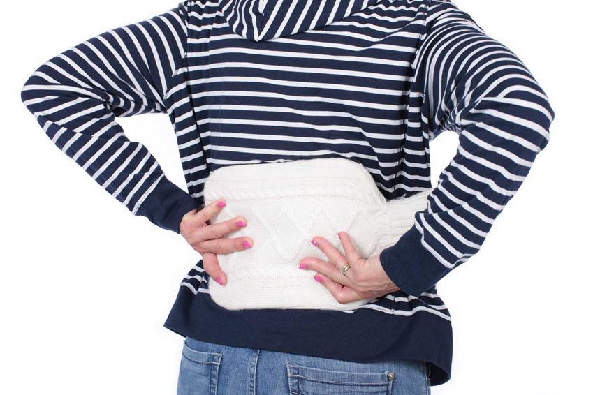 Termofor przyłożony do pleców, czyli domowe sposoby na rwę kluszową, a także jej objawy i ich leczenie domowe