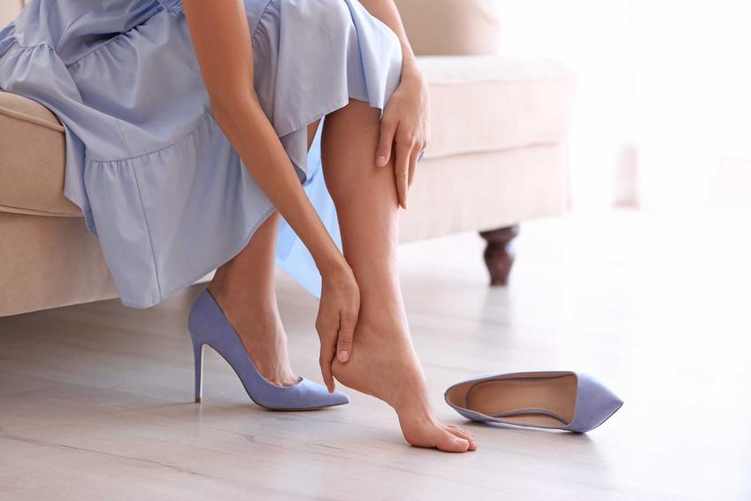 Kobieta z obolałymi stopami oraz najlepsze sposoby na obcierające buty na pięcie, domowe sposoby, środki na rozciąganie butów