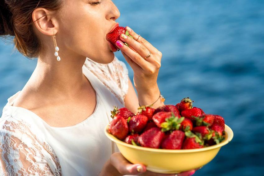 Kobieta jedząca truskawki oraz plamy z truskawek i porady jak sprać truskawki z ubrań krok po kroku domowymi sposobami