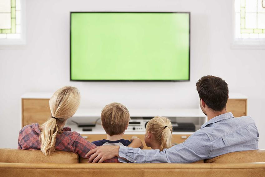 Rodzina przed TV oraz porady, na jakiej wysokosci powiesić telewizor i jak powiesić telewizor na ścianie
