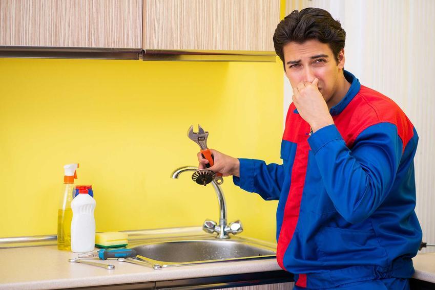 Mężczyzna zatykający nos nad zlewem, czyli przykry zapach ze zlewu i co zrobić, gdy śmierdzi ze zlewu